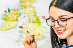 Young beautiful girl with glasses and map of England. Learning language concept. Attractive smiling girl points at map of the UK stock images