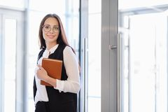 A young beautiful girl in eyeglasses enters glass office door. stock photography