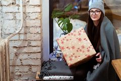 Young beautiful girl in glasses wrapped in a blanket siiting on the windowsill in a cafe stock photography