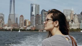 Young beautiful girl go for a boat through the East river in New York, America. Happy tourist on excursion in sunny day. stock video footage