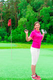 Young beautiful girl on a golf course. With a golf club Stock Photos