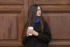 Young beautiful girl with gorgeous extra long hair in a black coat and blue scarf with disposable coffee cup having fun against wo Royalty Free Stock Images