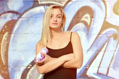 A young and beautiful girl graffiti artist with a paint spr stock images