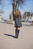Young beautiful girl in a gray coat. Back view Stock Photos