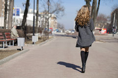 Young beautiful girl in a gray coat. Back view Stock Images