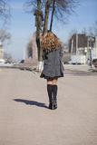 Young beautiful girl in a gray coat. Back view Royalty Free Stock Photo
