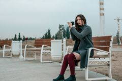 Young beautiful girl in a gray coat with vintage camera poses in the evening. Young beautiful girl in a gray coat with a vintage camera in her hands in the stock photos
