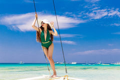 Young beautiful girl in a green bikini and straw hat, with long Royalty Free Stock Photography