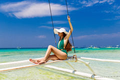 Young beautiful girl in a green bikini and straw hat, with long Stock Photo