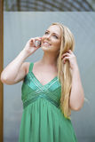 Young beautiful girl in the green dress talking on cell phone Royalty Free Stock Images