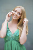 Young beautiful girl in the green dress talking on cell phone Stock Photos