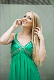 Young beautiful girl in the green dress talking on cell phone Royalty Free Stock Photo