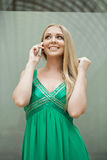 Young beautiful girl in the green dress talking on cell phone Royalty Free Stock Image