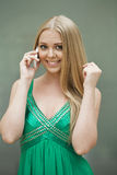 Young beautiful girl in the green dress talking on cell phone Stock Photo