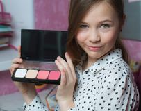 Young beautiful girl with green eyes, holding a pink eyeshadow s Royalty Free Stock Photography