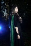 Young beautiful girl in green raincoat, looks as witch on Halloween in dark forest Stock Photo