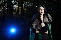 Young beautiful girl in green raincoat, looks as witch on Halloween in dark forest Stock Photos