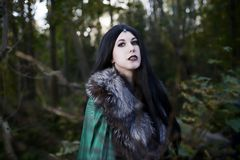 Young beautiful girl in green raincoat, looks as witch on Halloween in forest.  royalty free stock images