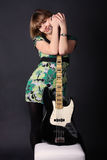 Young beautiful girl with a guitar. On a dark background Royalty Free Stock Photos
