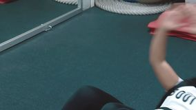 Young beautiful girl in the gym pumps the muscles of the press, lying on the karemate, close up stock video footage