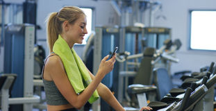 Young beautiful girl in gym, shaking her legs on cycling simulator, smiling at camera. The concept: to love sports, to attend a gy. M, proper nutrition, a Royalty Free Stock Photography