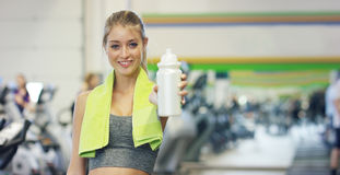 Young beautiful girl in the gym, stands smiling with a towel on her shoulder after the coaching and relaxed. Concept: to love spor. Ts, to attend a gym, proper Royalty Free Stock Photos
