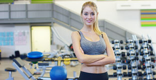 Young beautiful girl in the gym, stands smiling with a towel on her shoulder after the coaching and relaxed. Concept: to love spor. Ts, to attend a gym, proper Royalty Free Stock Images