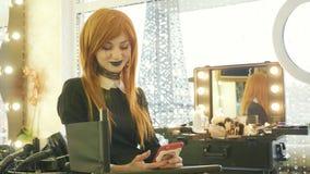 Young beautiful girl with halloween makeup using smart phone at beauty salon. Young beautiful girl with halloween makeup sits on the chair and using smart phone stock video
