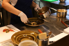 Young beautiful girl hands cook pours bowl ready-made meals in c Royalty Free Stock Photo
