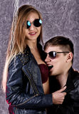 Young beautiful girl and handsome guy in leather jackets and sunglasses posing on a high chair and kissing on gray Stock Photography