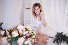 Young beautiful girl happy, the woman fun laughs after receiving a bouquet of flowers. Glamour portrait of beautiful woman model with fresh daily makeup and royalty free stock images