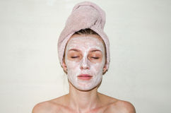 The young beautiful girl has caused a cosmetic mask, white face cream skin health, stands on a light background after bath with a Royalty Free Stock Photo