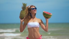 Young beautiful girl has fun at the beach near sea dancing with tropical fruit. Concept joy and healthy food. Young beautiful girl has fun at the beach near sea stock video