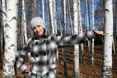 The young beautiful girl has leant about a birch. The young beautiful girl in a checkered coat has leant about a birch stock images