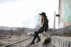 Young beautiful girl in a hat and with a dark make-up outside. G. Irl in the Gothic style on the street. A girl walks down the city street in a leather waistcoat Royalty Free Stock Image