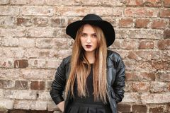 Young beautiful girl in a hat and with a dark make-up outside. G. Irl in the Gothic style on the street. A girl walks down the city street in a leather waistcoat Royalty Free Stock Photo