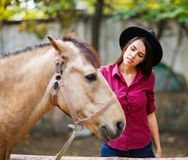Young beautiful girl in a hat and shirt stroking a horse. Outside. royalty free stock images