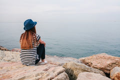 Young beautiful girl in a hat sits on the rocks on the seashore and looks into the distance. Rest, vacation, relaxation. Stock Image