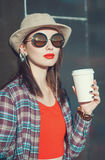 Young beautiful girl in hat and sunglasses with cup of coffee Royalty Free Stock Image