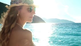 Young beautiful girl in hat and sunglasses standing on a beach at sunset stock video