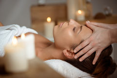 Young beautiful girl having face massage relaxing in spa salon. Stock Photo