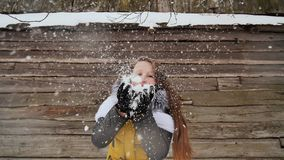 Young beautiful girl having fun blowing snow on the camera in winter clothes on the background of a wooden house in the stock footage