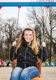 Young beautiful girl having fun riding a chain-swing in the park Stock Photo