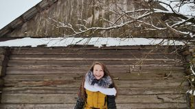 Young beautiful girl having fun throwing snow, posing on camera in winter clothes on background of wooden house in stock footage