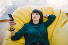 Young beautiful girl hipster lies back and enjoys light mobile phone. Bag chair in a modern office. Indoor Portrait. The young beautiful girl lies back and Stock Photos