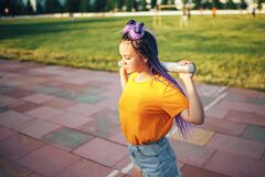 Young beautiful girl holding a baseball bat in a yellow open-air t-shirt in a sports stadium