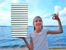 Girl with a bunch of books. Young beautiful girl holding a bunch of books in one hand. The second hand shows the OK sign. The concept of a smart child, ease of stock image