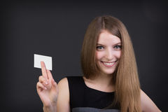 Young beautiful girl holding a business card in hand. Studio picture Stock Photos