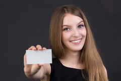 Young beautiful girl holding a business card in hand. Studio picture Royalty Free Stock Photo