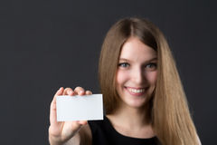 Young beautiful girl holding a business card in hand. Studio picture Stock Photo